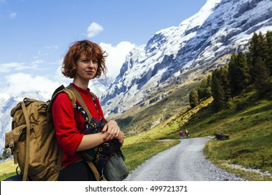Pretty, red haired, european girl, dressed in red sweater, black leggings and a pair of braces, standing on the path in the swiss Alps with the backpack on her back. .