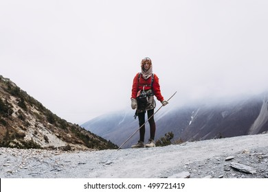 Pretty, red haired, european girl standing on the trail surrounded by stones, snow and ice in Himalaya mountains. Nepal.