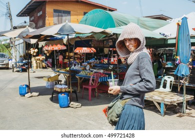 Pretty, red haired, european girl standing on the sun in the market on the street. She's a hood on her head, she is holding a drink and smiling. Malaysia.