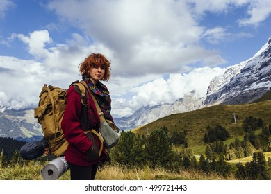 Pretty, red haired, european girl, dressed in red sweater, black leggings, standing on the path in the swiss Alps with the backpack on her back. Switzerland.