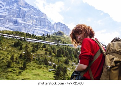 Pretty, red haired, european girl, dressed in red sweater, black leggings and a pair of braces, standing on the path in the swiss Alps with the backpack on her back. Switzerland.