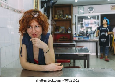 Pretty, red haired, european girl sitting and smiling in the asian restaurant with her hands on the table. Thailand.