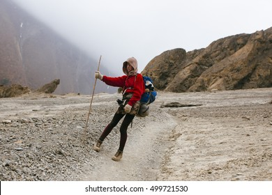 Pretty, red haired, european girl standing on the trail surrounded by stones and misty, cloudy Himalaya mountains, Nepal.