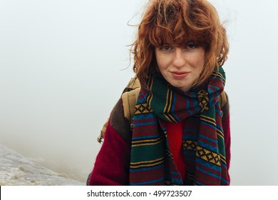 Pretty, red haired, european girl, dressed in red sweater and woolen scarf is standing in the mist on the edge of the limbo in the mountains, with the backpack on her back. Switzerland.