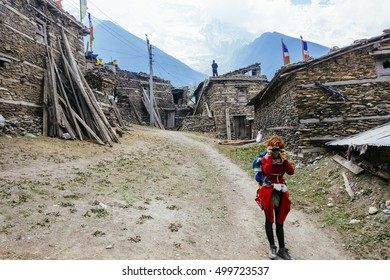Pretty, red haired, european girl taking photo in the tibetan village in Nepal.