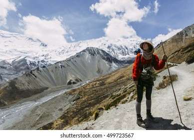 Pretty, red haired, european girl standing on the trail surrounded by stones, snow and ice in Himalaya mountains, leaning on the bamboo stick. Nepal.