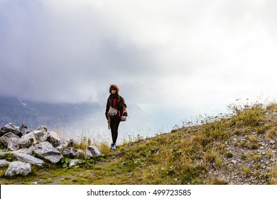 Pretty, red haired, european girl, dressed in red sweater and woolen scarf is standing in the mist in the mountains, with the backpack on her back, Switzerland.