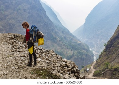 Pretty, red haired, european girl standing on the trail surrounded by stones in the mountains. Annapurna Circuit, Himalayas, Nepal.