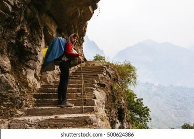 Pretty, red haired, european girl standing on the stairs, surrounded by stones in the mountains, leaning on the bamboo stick. Annapurna trail, Himalayas, Nepal.