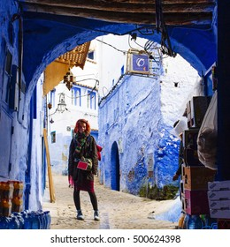 Pretty, red haired, european girl standing on the street under the arch in the  blue city, Chefchaouen, Morocco.