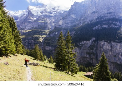 Pretty, red haired, european girl standing on the trail full of sun, surrounded by the mountains, Switzerland.