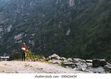 Pretty, red haired, european girl standing on the trail surrounded by stones and plants in the mountains, leaning on the bamboo stick. Annapurna Circuit, Himalayas, Nepal.