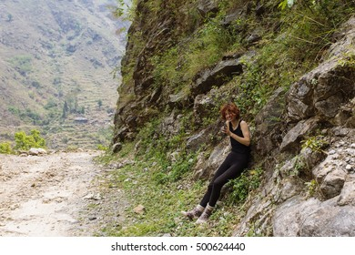 Pretty, red haired, european girl leaning on the rocky wall in the mountains. Annapurna trek, Himalayas, Nepal.