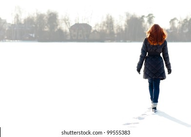 Pretty red haired girl walking on frozen lake and making footpath