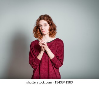 Pretty red-haired girl in confusion isolated on a gray background
