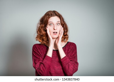 Pretty red-haired girl was shocked, isolated on a gray background