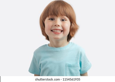 pretty red-haired kid showing his white teeth to the camera. little healthu boy wearing blue T-shirt