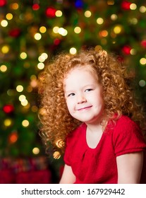 Pretty red-haired little girl wearing red dress sitting in front of Christmas tree with colorful lights