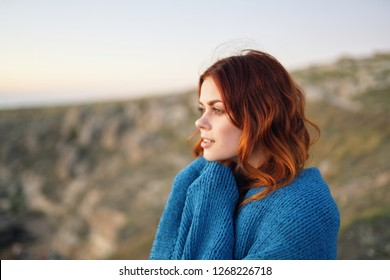 A pretty red-haired woman covered in a blanket in nature