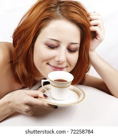 Pretty red-haired woman in white nightie lying in the bed near cup of coffee