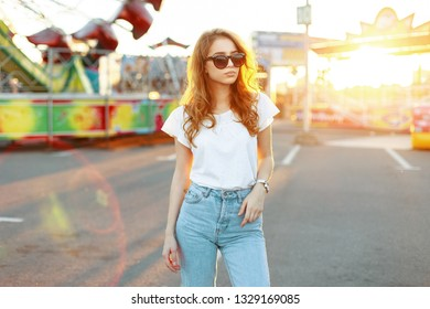 Pretty redhead beautiful young hipster woman in stylish T-shirt in vintage jeans in trendy sunglasses is walking in an amusement park. Cute fashion model girl enjoys an orange summer sunset.