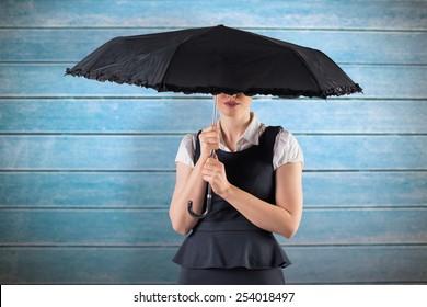 Pretty redhead businesswoman holding umbrella against wooden planks