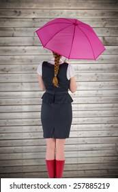 Pretty redhead businesswoman holding umbrella against wooden planks background