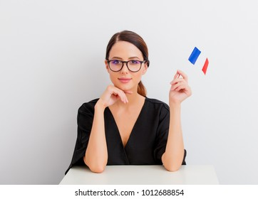 Pretty redhead caucasian woman in black dress with french flag sitting at white table in lagom style on white background