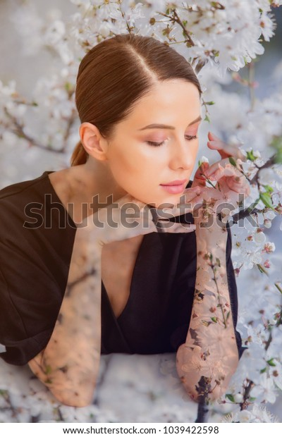 Pretty redhead caucasian woman in black dress sitting at white table in lagom style on white background and blossom cherry tree