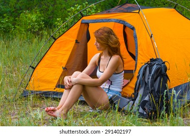 pretty redhead girl sit near a touristic tent
