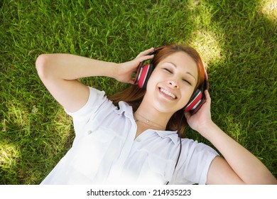 Pretty redhead lying on grass listening to music on a sunny day