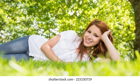 Pretty redhead lying on the grass smiling at camera on a sunny day