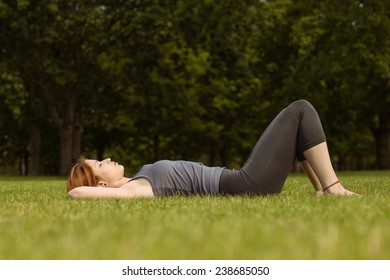 Pretty redhead lying on grass in park