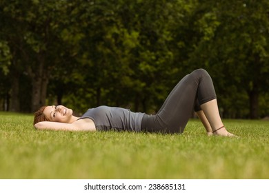 Pretty redhead lying and smiling in park at sunshine