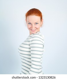 Pretty redhead smiling woman posing against light background