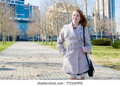 Pretty redhead woman with a lovely friendly smile leaning against a brick wall in an urban environment beaming at the camera, close up head and shoulders