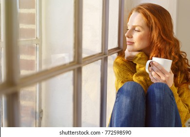 Pretty redhead woman savoring her mug of hot coffee as she sits on a window sill with eyes closed in contentment