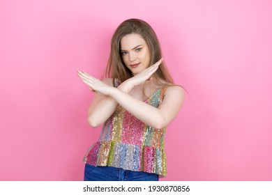 Pretty redhead woman wearing a shiny top standing over pink background Rejection expression crossing arms doing negative sign, angry face