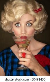 Pretty retro blonde woman in vintage 50s dress with martini