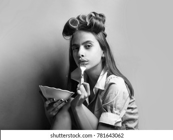 Pretty retro girl young sexy cute woman with curlers in long vintage hair in fashionable shirt of maid uniform or housewife on grey background holds white plate and fork ready to eat