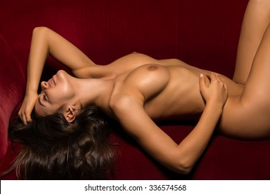 Pretty Romanian brunette lying nude on a red couch