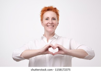 Pretty romantic mature redhead woman making a heart gesture with her fingers in front of her chest showing her love and affection with a happy tender smile. Concept of healthcare