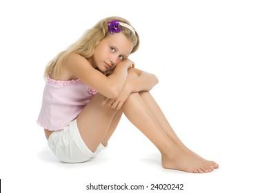 Pretty sad teenage girl sit on floor isolated on white