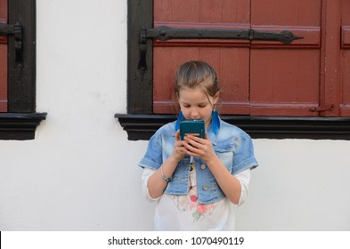 Pretty school age girl touching smart phone in the town, technology for children