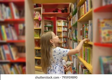 pretty school girl in library choosing books.
