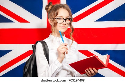 Pretty school girl over British flag in white shirt and glasses. Study english concept.