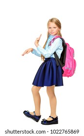 Pretty schoolgirl in elegant school uniform posing at studio with positive emotions. Isolated over white background. School fashion. Copy space.