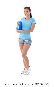 Pretty schoolgirl wearing shorts and t-shirt, smiling, holding folder.?