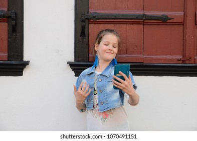 Pretty scool age girl making selfie by smartphone in the old town