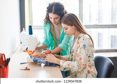 Pretty seamstress teaching girl working with sewing machine at sewing classes with window on background in modern sewing workshop